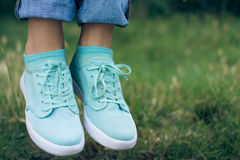 Female legs in jeans and sport shoe floating in the air above th. E green grass in the park. Flying sneakers outdoors. Conceptual image Royalty Free Stock Images