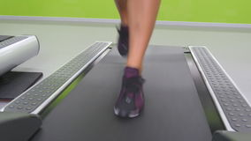 Female legs jogging and running on treadmill in gym. Young woman exercising during cardio workout. Feet of girls in stock video