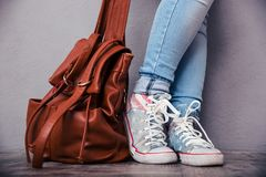 Female legs with leather backpack. Closeup portrait of female legs with leather backpack Stock Photo