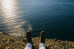 Female legs in leather boots are on the edge of a cliff. Close up of female legs in leather boots are on the edge of a cliff Royalty Free Stock Photography