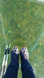 Female legs in leather boots standing on cracked ice, top view Stock Image