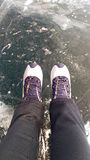 Female legs in leather boots standing on cracked ice, top view Royalty Free Stock Images