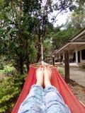 Female legs lie in a red hammock stock photo