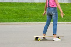 Female legs with a longboard closeup.Girl is preparing to ride on the board. For Copy Space. royalty free stock images