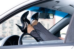 Female legs are lying on steering wheel Royalty Free Stock Photography