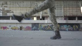 Female legs in military uniform marching on the concrete floor in dusty dirty abandoned building. The concept of a. Female legs of a young woman in military stock video footage