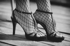 Female legs in net stockings and high heels. Outdoor photo Stock Image