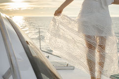Female legs outside of yacht under warm sunset flare Royalty Free Stock Photography