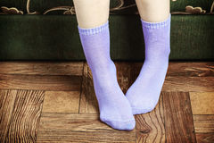 Female legs overhang from the sofa in purple socks Stock Images