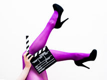 Female legs in pink pantyhose and black high heels with movie cl Stock Images