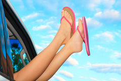 Female legs in pink sandals. Out from the car. Summer trip concept Royalty Free Stock Images