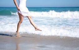 Female legs playing in ocean. Female leg walking on the beach in the ocean stock images