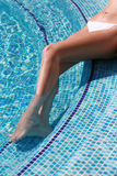 Female legs in pool. Suntanned female legs in pool with transparent water Stock Image