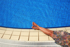 Female legs in the pool water Stock Image