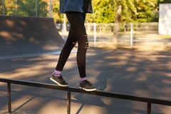 Female legs in ragged black jeans and black sneakers. Royalty Free Stock Image
