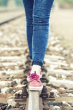 Female legs on the rail. Female legs in sneakers on the rail of the railway - colorized photo Royalty Free Stock Photography
