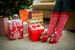 Female legs in red christmas socks Royalty Free Stock Images