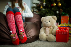 Female legs in red christmas socks with teddy bear Royalty Free Stock Photography