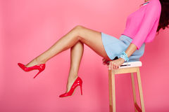 Female legs with red heels. Beautiful female legs with red heels on pink background. Girl in short blue skirt sitting on a bar stool Stock Image