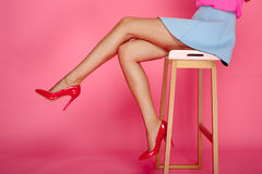 Female legs with red heels. Beautiful female legs with red heels on pink background. Girl in short blue skirt sitting on a bar stool Stock Images