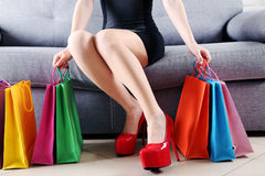 Female legs with red high heels. And shopping bags on grey sofa Stock Images