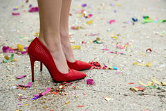 Female legs in red shoes against the confetti and garlands. Selective focus, copy space Stock Photos