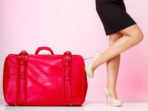 Female legs with red suitcase on pink. Travel. Stock Photos