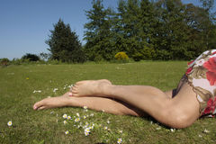 Female legs relaxing on grass lawn Royalty Free Stock Image