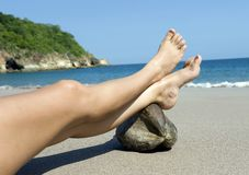 Female legs resting on coconut tropical beach Royalty Free Stock Photo