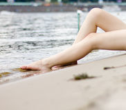 Female legs on a river background Stock Image