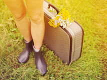 Female legs in rubber boots, an old suitcase and a bouquet of wild flowers on a green grass in summer sunny day. Stock Images