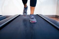 Female legs running on treadmill. Closeup portrait of a female legs running on treadmill Stock Photos