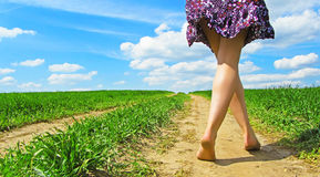 Female legs on rural road Royalty Free Stock Image