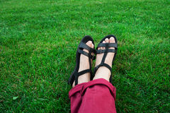 Female legs in sandals on background of green grass Stock Photography