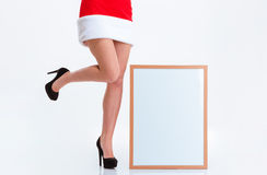 Female legs in santa claus cloth and blank board Royalty Free Stock Image
