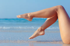 Female legs on sea background. Female legs on blue sea background, side view Stock Image