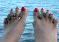 Female legs on sea procedures with stones between fingers Stock Images