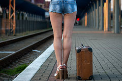 Female legs, in sexy shorts in shoes with an old suitcase on the Stock Photos