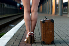 Female legs, in sexy shorts in shoes with an old suitcase on the. Station platform Stock Image
