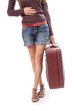 Female legs in shorts and suitcase in hand Stock Images