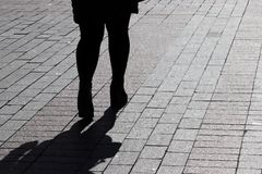 Silhouette of lonely woman walking down the street, black shadow on pavement. Female legs on the sidewalk, concept of loneliness, parting, diet, dramatic life royalty free stock photos