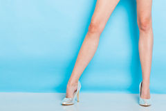 Female legs in silver high heels shoes. Female fashion. Silver high heels spiked fashionable shoes on long legs. Studio shot against blue royalty free stock photo