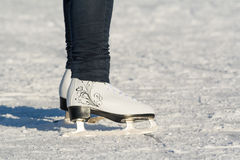 Female legs in skates. On the snow Royalty Free Stock Photo