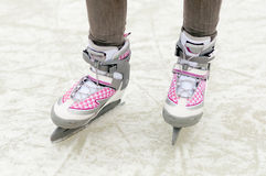 Female legs in skates standing on ice Stock Photo