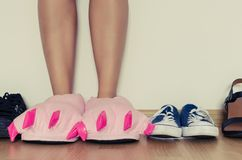 Female legs in slippers. Female legs in cute pink monster foot slippers with big claws between different kind of shoes. Stay comfortable concept Stock Photo