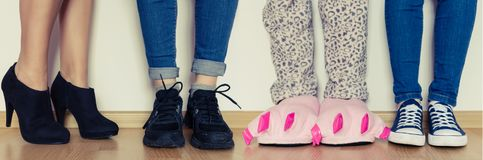 Female legs in slippers and different kind of shoes. Female legs in cute pink monster foot slippers with big claws and other in different kind of shoes. Be stock image