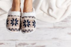 Female legs in slippers. Against the background of a wooden floor. Cozy, warm and comfortable slippers on the feet royalty free stock photography