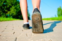 Female legs in sneakers close up running down the road. In the morning Royalty Free Stock Images