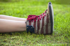 Female legs in sneakers with the design of the American flag on Royalty Free Stock Images