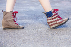 Female legs in sneakers with the design of the American flag on Stock Photography